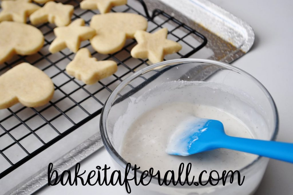 vanilla icing in a bowl next to cookies on a cooling rack