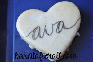 """ava"" on a cookie with lines drawn down for calligraphy"