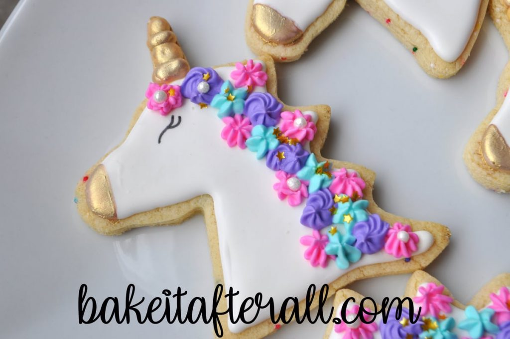 Gold luster dust painted on horn and nose of unicorn cookies