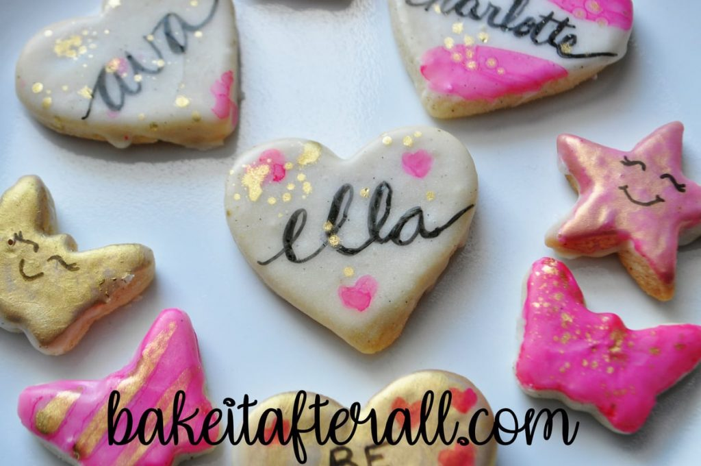 "plate of painted watercolor cookies with a heart shaped Cookie that says ""Ella"" in calligraphy"