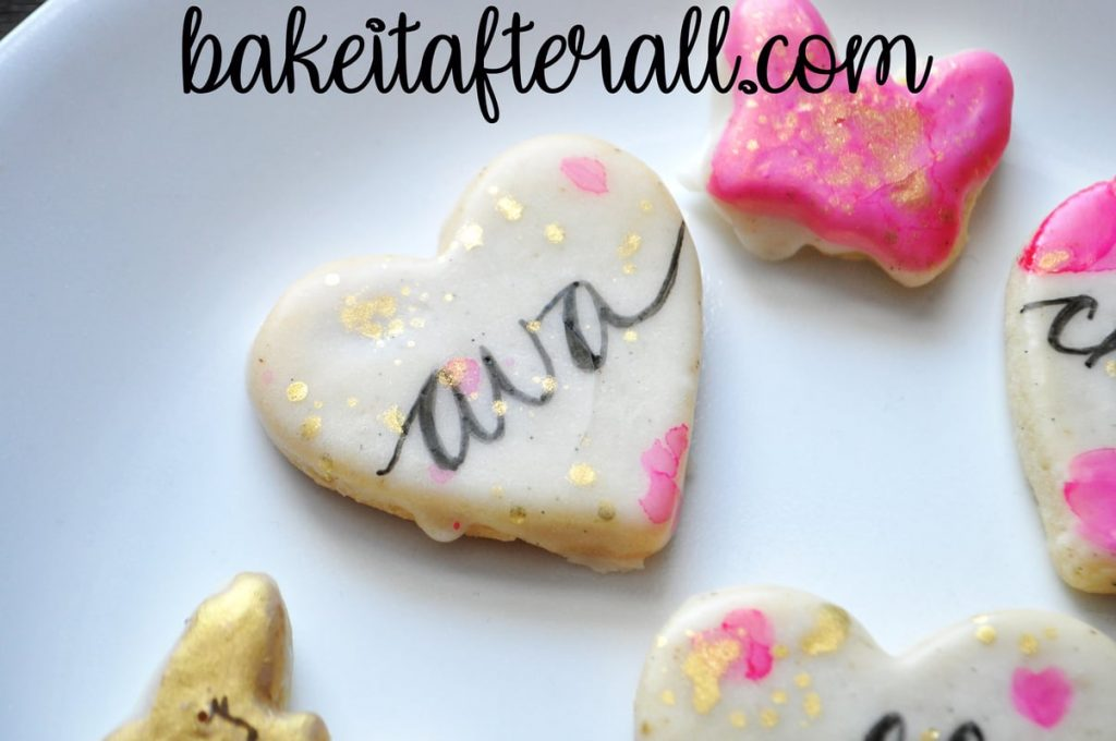 "cookie that says ""Ava"" in calligraphy and splattered with gold luster dust"