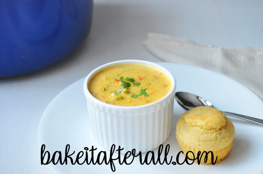 gluten free broccoli cheddar soup in a bowl with a corn muffin