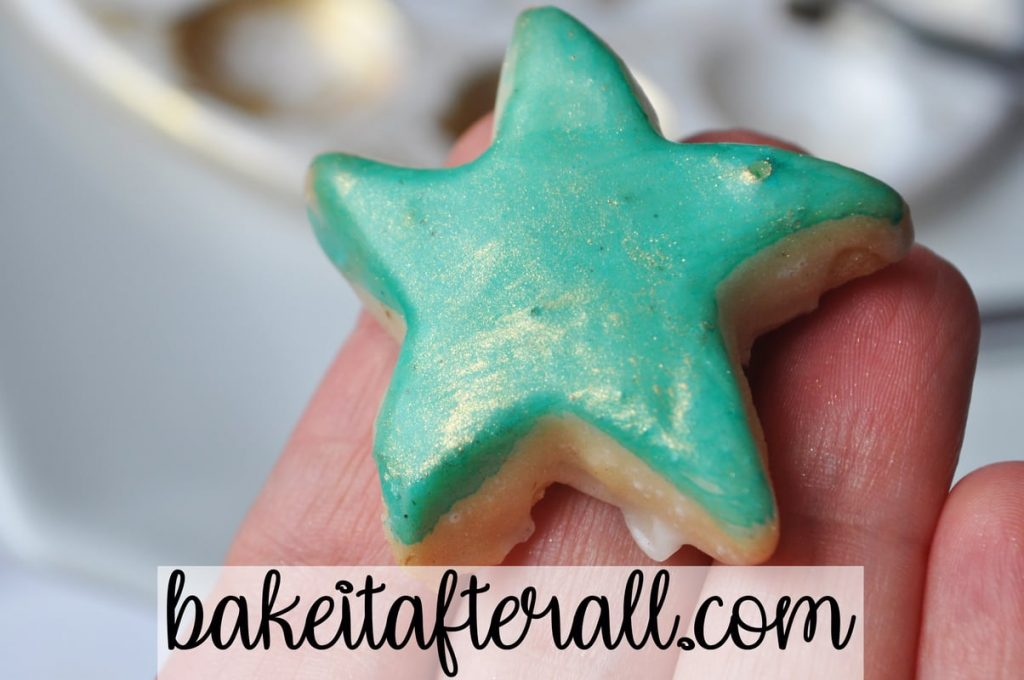 Starfish Cookie held up to show the gold luster dust on top of the teal paint
