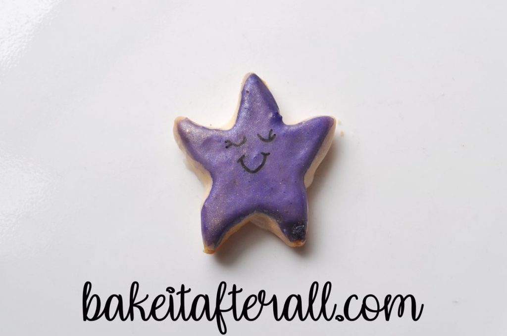 Starfish cookie with a black smile drawn on using a food coloring marker