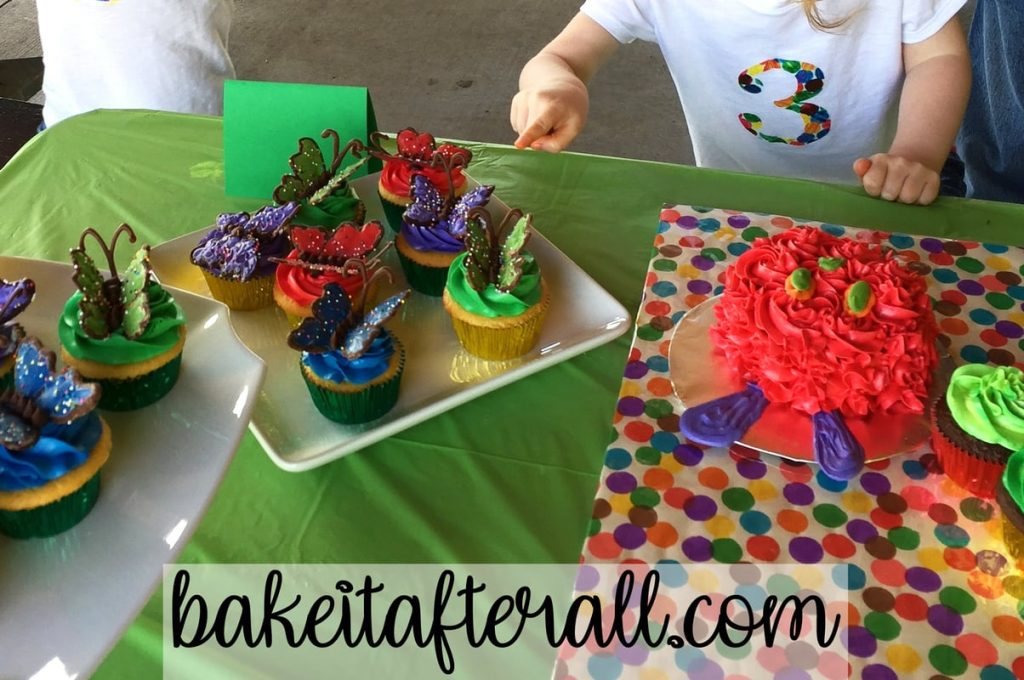 kid pointing to butterfly cupcakes
