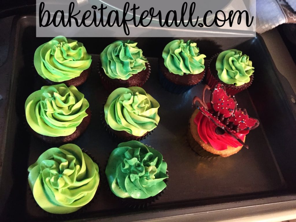 green frosted cupcakes in a cake pan for transporting