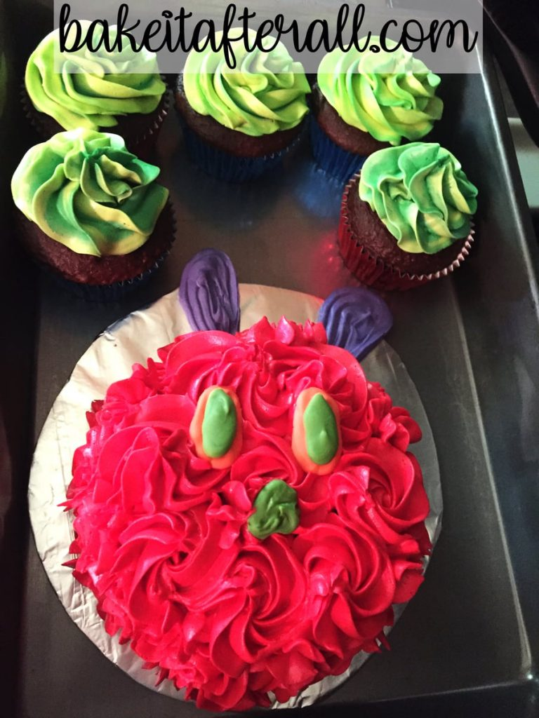 green frosted cupcakes and red frosted caterpillar head in a cake pan for transporting