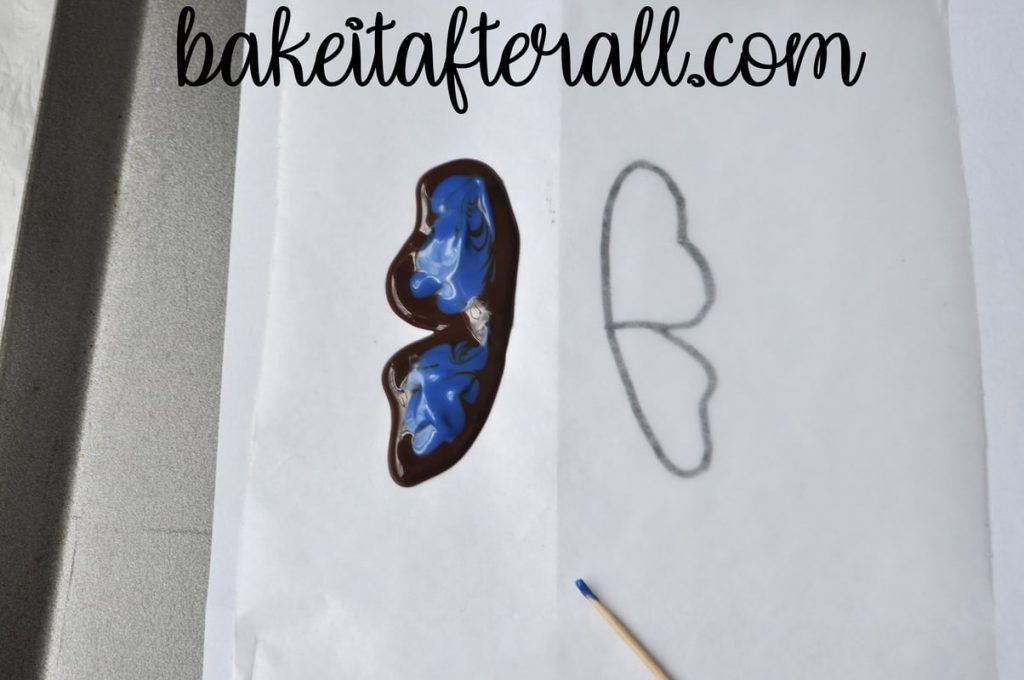 butterfly wing outlined with chocolate and filled with melted blue candy melts