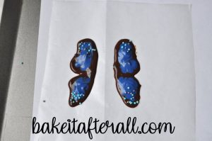 two butterfly wings outlined with chocolate and filled with melted blue candy melts