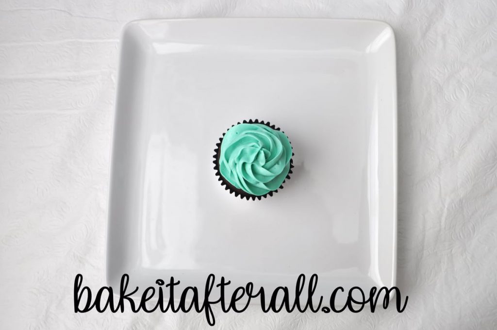 single cupcake with blue buttercream piped on top