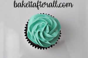 up close of single cupcake with blue buttercream piped on top