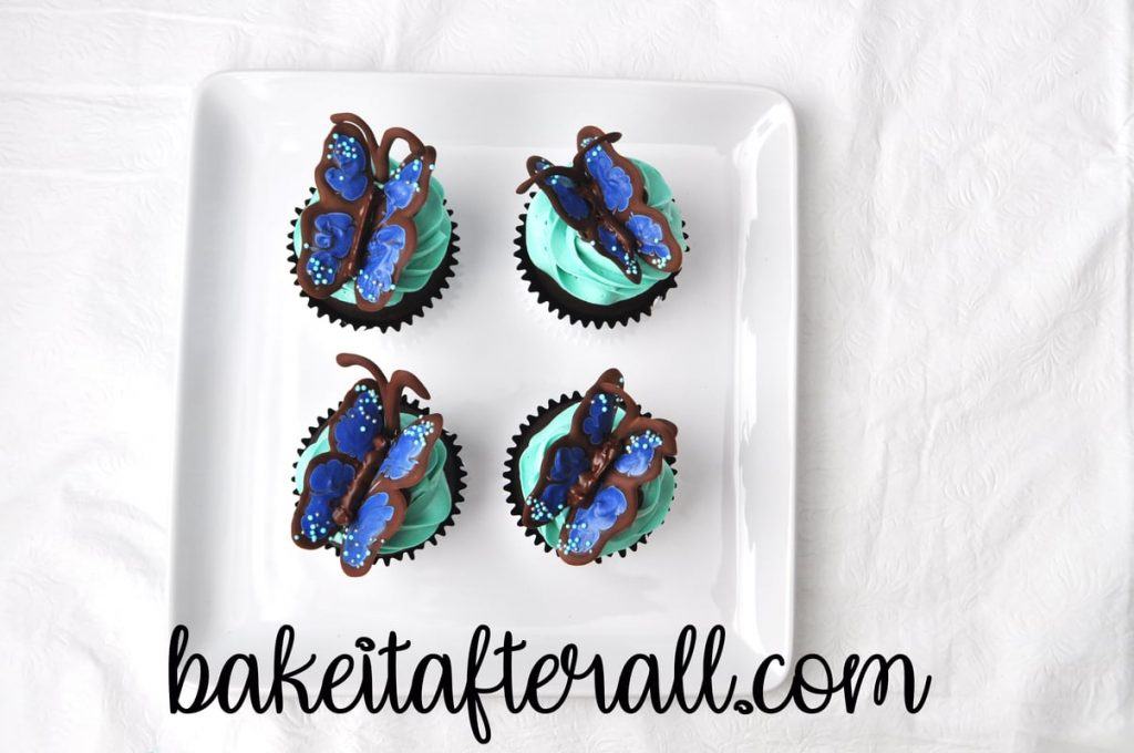 4 assembled butterfly cupcakes on a white plate